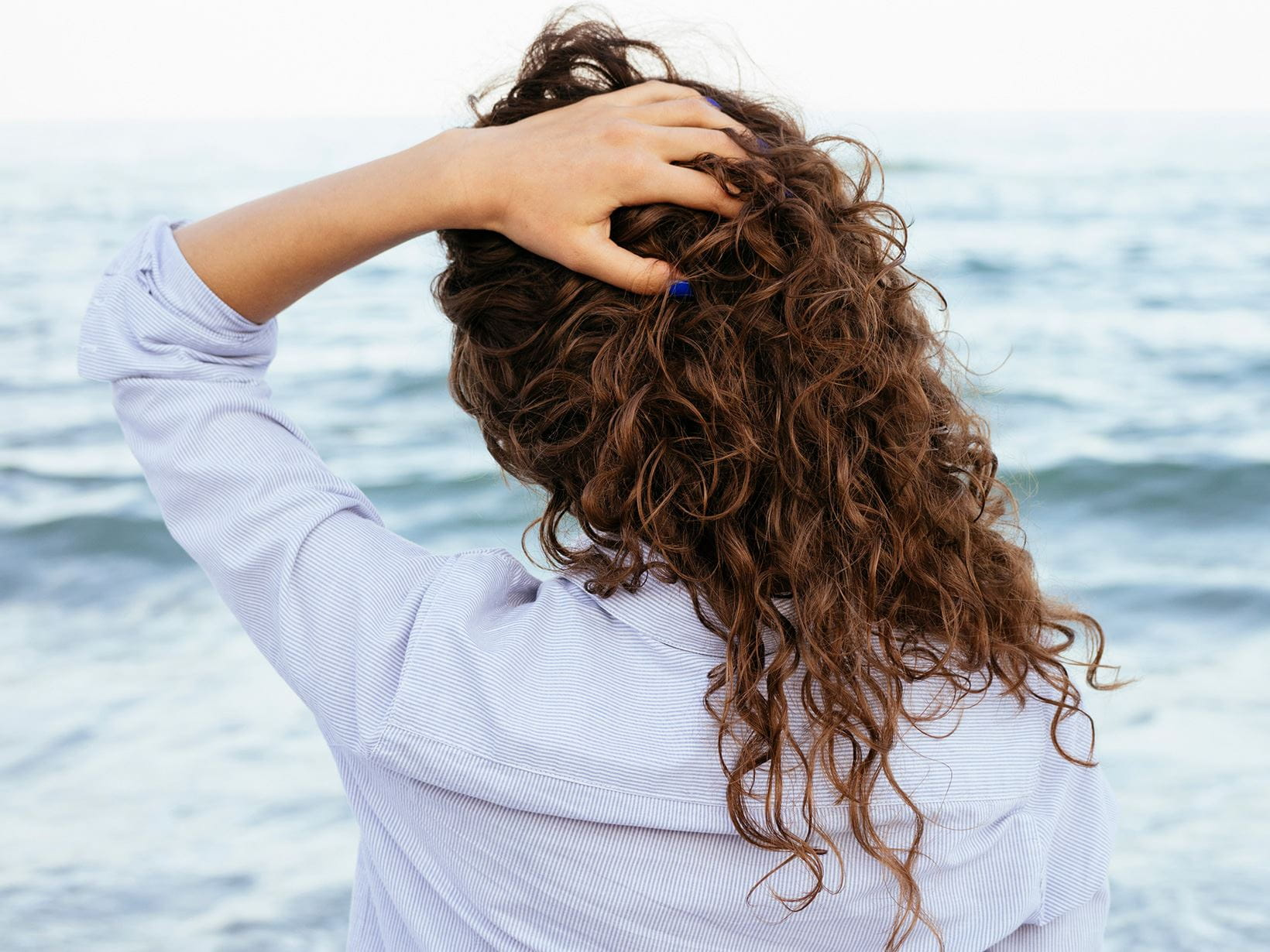 young-woman-with-curly-hair-looking-at-sea